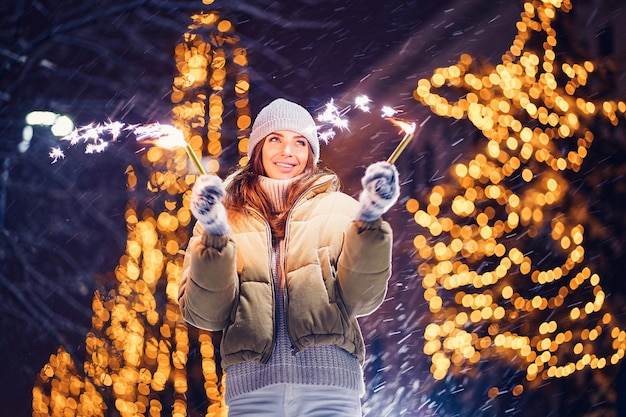 Beautiful woman holding sparkles and have fun in the open air