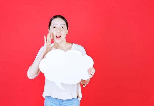 Beautiful woman holding speech bubble with a cloud shape