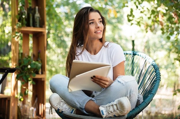 Beautiful woman holding a textbook while sitting in a chair