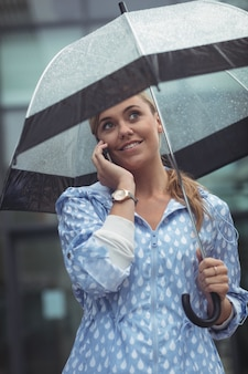 Beautiful woman holding umbrella while talking on mobile phone