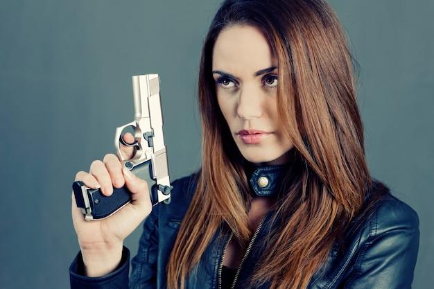 Красивая женщина, подняв ее пистолет