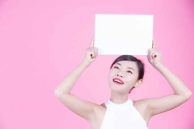 Beautiful woman holding a white board sheet on a pink background.