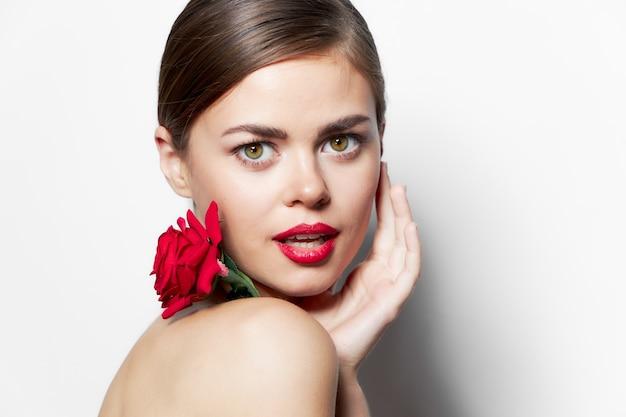 美しい女性は、豪華な口紅で顔の近くに手を握ります。