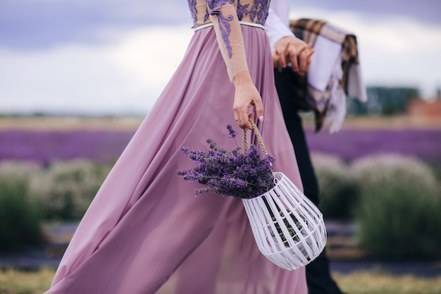Beautiful woman holds bouquet of flowers lavender in basket while walking outdoor through wheat field in summer.