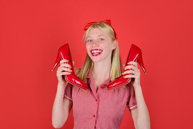 Красивая женщина держит элегантные красные туфли, счастливая взволнованная женщина держит стильные туфли красивая девушка в красном