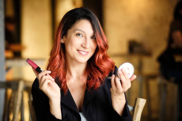 Красивая женщина держит макияж на руках, чтобы нанести его на лицо