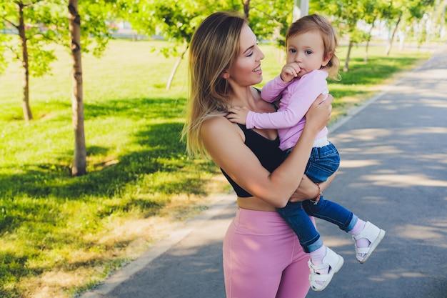 美しい女性は、公園で彼女の腕の中で1歳の赤ちゃんを保持しています。