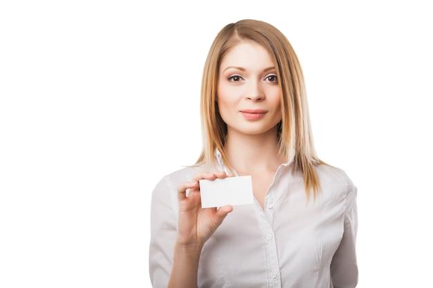 Красивая женщина протягивает бизнес или кредитную карту изолированного на белом фоне
