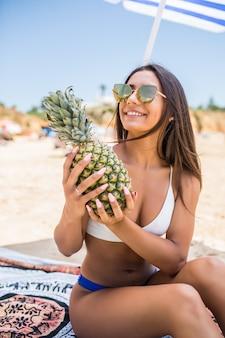 美しい女性は、リラックスしたビーチ熱帯の手にパイナップルを保持しています。彼女の手でトロピカルフルーツを持つ美しい女性モデル