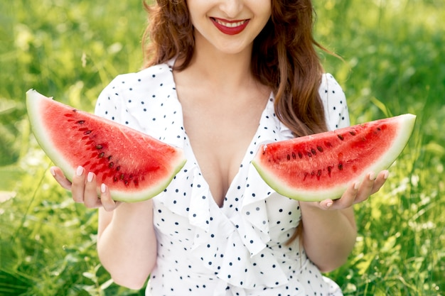 Beautiful woman holds two pieces of watermelon.