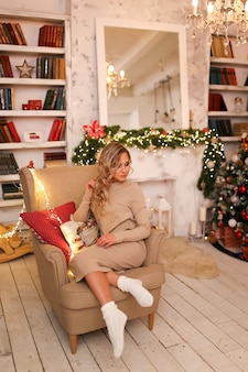 A beautiful woman in a home dress and warm socks relaxes by the fireplace and christmas tree