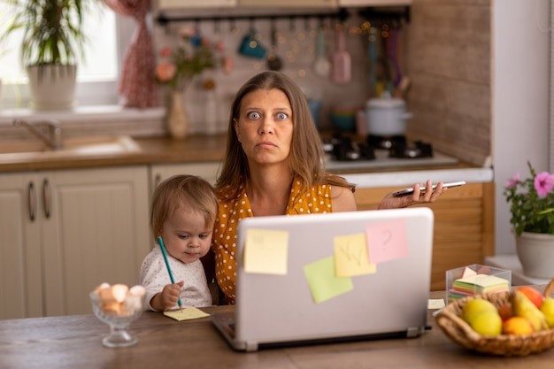 Beautiful woman at home in the kitchen uses naotbook and tries to work with a small child in her arms