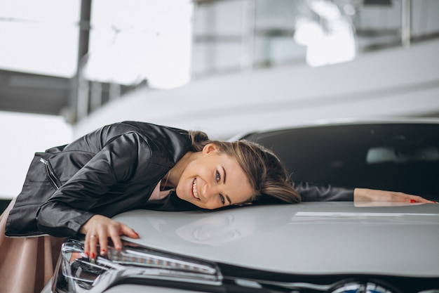 Beautiful woman hugging a car