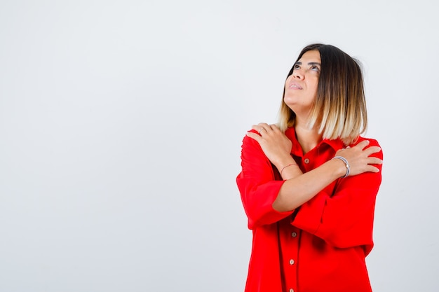 Beautiful woman hugging herself, looking up in red blouse and looking wondered. front view.