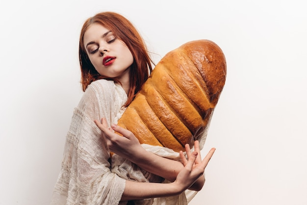 Beautiful woman hugging loaf with her hands makeup transparent fabric on her shoulders.