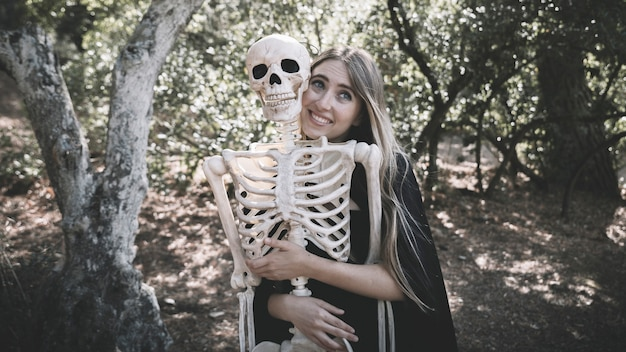 Beautiful woman hugging behind skeleton
