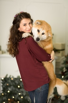 Beautiful woman hugs, cuddles with her akita inu dog