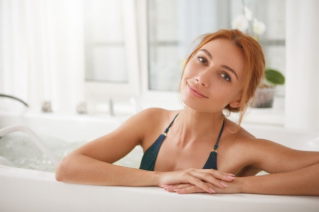 Beautiful woman in hydro massage tub at spa center