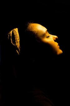暖かいオレンジ色の光に照らされた美しい女性。インスピレーションのコンセプト
