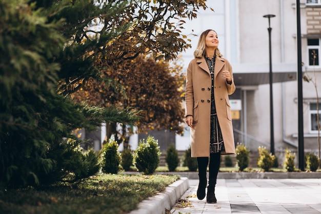 공원에서 외부 베이지 색 코트에서 아름 다운 여자