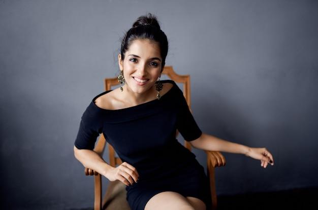 의자 럭셔리 패션 고립 된 배경 근처 검은 드레스에 아름 다운 여자
