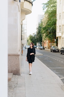 도시 풍경의 배경에 검은 드레스에서 아름 다운 여자