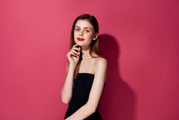 黒のドレスピンクの背景の美しい女性。高品質の写真