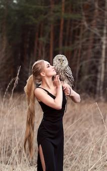 Красивая женщина в черном платье с совой на руке. блондинка с длинными волосами на природе держит сову. романтический нежный образ девушки