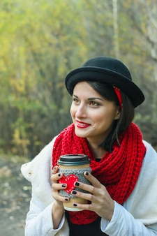 검은 모자를 쓴 아름다운 여성이 손에 아늑한 컵을 들고 있습니다. 밝은 미소와 좋은 분위기