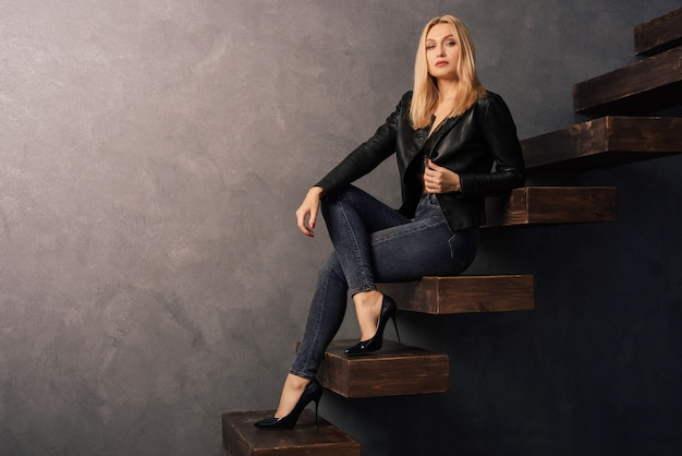 黒革のジャケットとジーンズ、木製のカンチレバーのはしごに座っているかかとの美しい女性