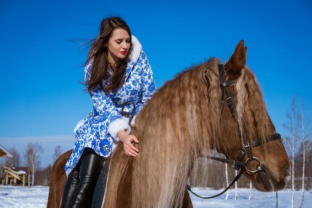 晴れた日に冬に馬に乗って青いコートの美しい女性