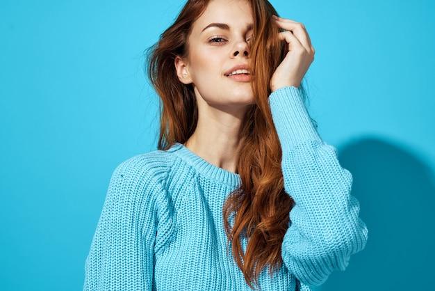 青いセーターの孤立した背景の美しい女性