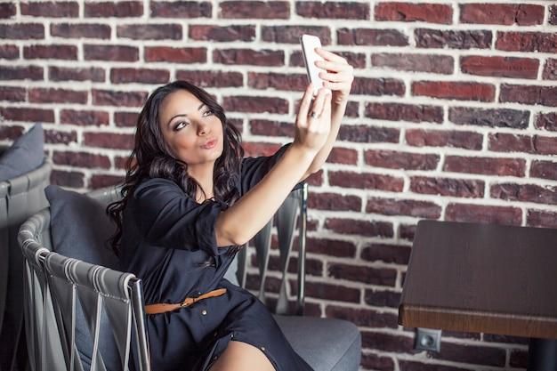 レストランの椅子に座っている美しい女性がモバイルで自分撮りをしています。公共の場でのスマートフォンによるコミュニケーション