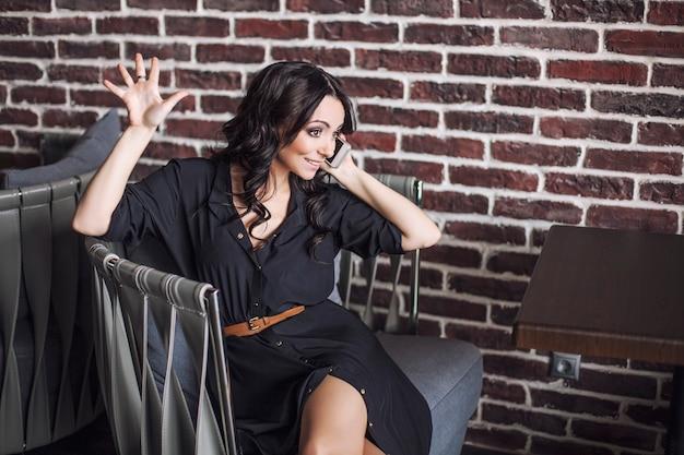 電話でレストランの椅子に座っている美しい女性。公共の場でのスマートフォンによるコミュニケーション