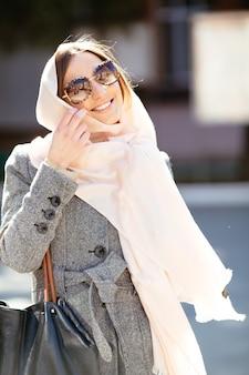 Красивая женщина в пальто позирует на улице