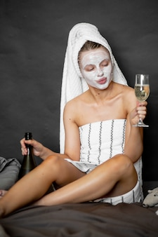 화장품 마스크와 수건에서 아름 다운 여자는 유리에 샴페인을 부어 침대에 앉아 웃고