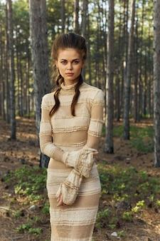 Красивая женщина в платье с головкой прически в стиле ретро романтический лес.