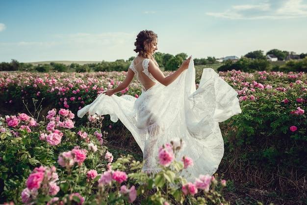 花の公園、庭のバラの美しい女性。メイク、髪、バラの花輪。ロングウェディングドレス。自由奔放に生きるスタイルの女性
