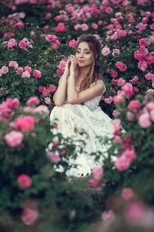 꽃 공원, 정원 장미에서에서 아름 다운 여자. 메이크업, 헤어, 장미 화환. 긴 웨딩 드레스. boho 스타일의 여자