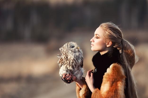 彼の腕にフクロウと毛皮のコートで美しい女性。フクロウを保持している自然の中で長い髪のブロンド。女性のロマンチックな繊細なイメージ