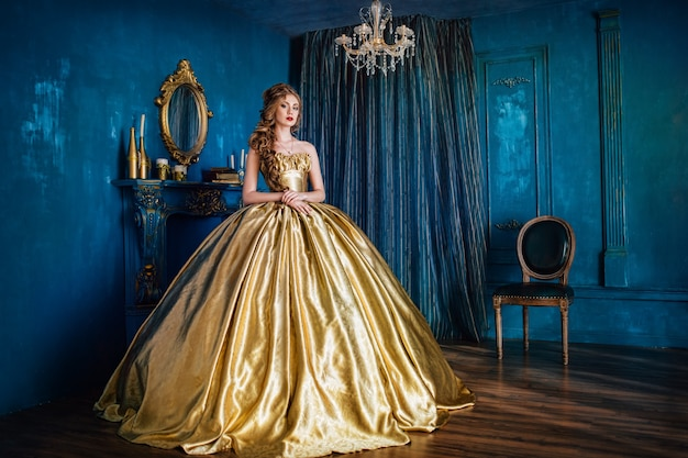 Красивая женщина в золотом бальном платье в большом синем интерьере