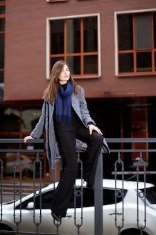 Красивая женщина в сером пальто и синем шарфе над зданием с окнами. молодая женщина сидит на перилах и кокетливо смотрит
