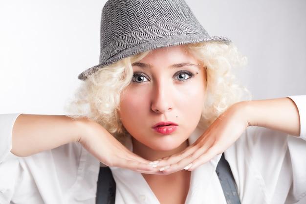 帽子のビジネススタイルの美しい女性顔の近くで彼女の手を保持しているブロンドの女の子