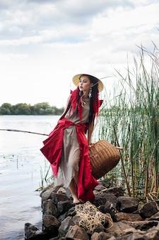 川沿いのアジアンスタイルの帽子の美しい女性