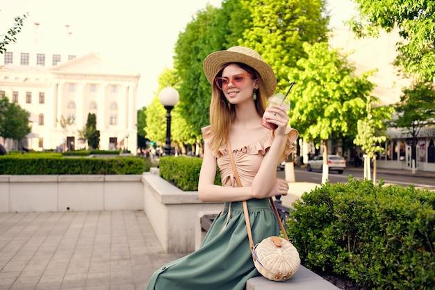 Красивая женщина в шляпе в парке пьет отдых на свежем воздухе