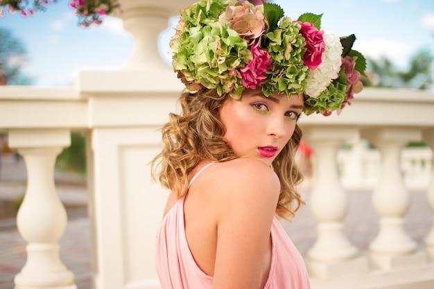 彼女の頭の上に花と光のピンクのドレスで美しい女性