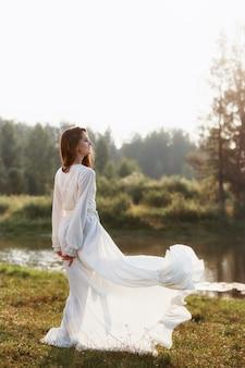 호수 근처에 서 있는 긴 흰색 드레스를 입은 아름다운 여자