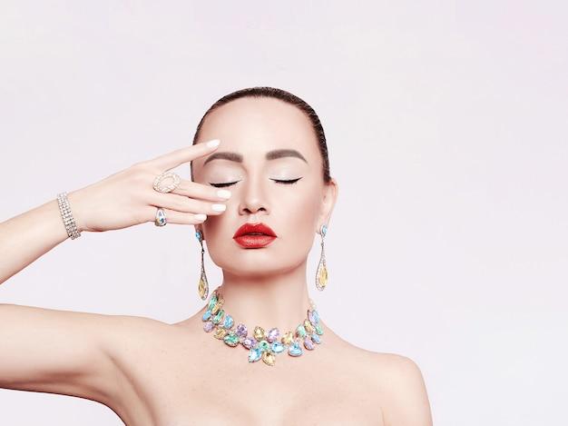 Красивая женщина в колье, серьгах и кольце. модель в украшениях из драгоценных камней, бриллиантов.