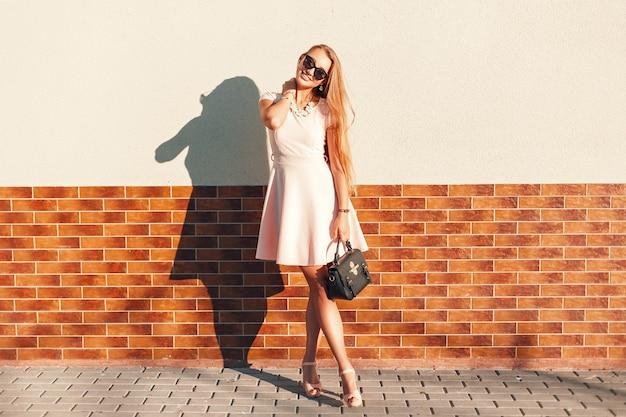 Красивая женщина в розовом платье с сумочкой в солнечный день, стоя у стены