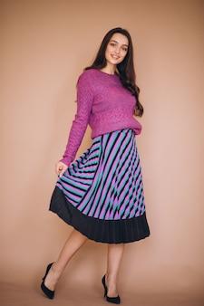 Красивая женщина в фиолетовом свитере и юбке